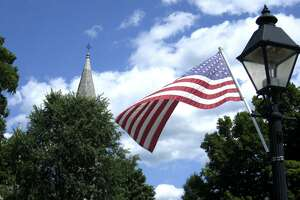File photo of the American flag along Main Street in New Milford with the steeple of St. John's Episcopal Church in the background.