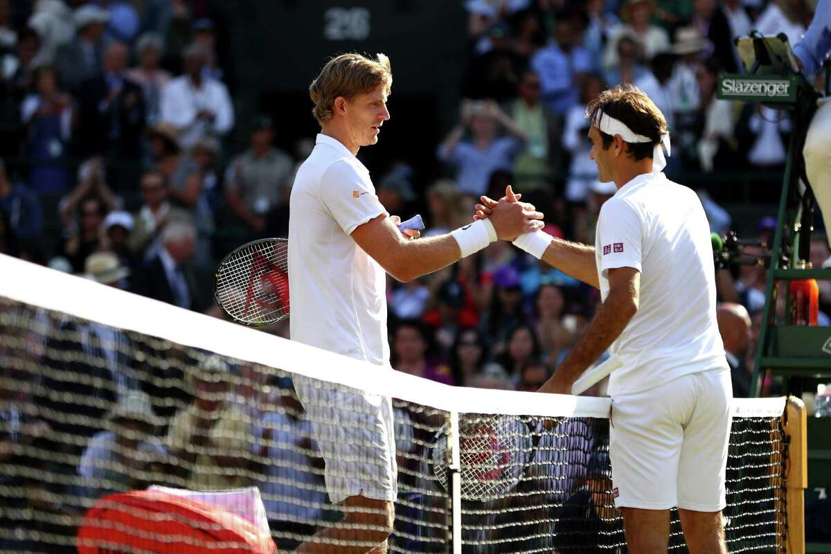 LONDON, ENGLAND - JULY 11: Kevin Anderson of South Africa and Roger Federer of Switzerland embrace at the net following their Men's Singles Quarter-Finals match on day nine of the Wimbledon Lawn Tennis Championships at All England Lawn Tennis and Croquet Club on July 11, 2018 in London, England. Anderson won the match 6-4, 7-6, 5-7, 4-6, 11-13 in 4hr 13min.