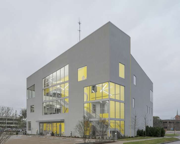 A full-height vertical circulation atrium greets visitors. The yellow wall acts as threshold to the interior program spaces and telegraphs through the muted facade.
