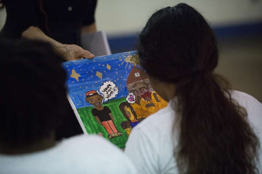 A juvenile offender asks to take a look at a painting making reference to domestic violence, Sunday, June 17, 2018, at the Harris County Juvenile Facility in Katy. Photo: Marie D. De Jesús
