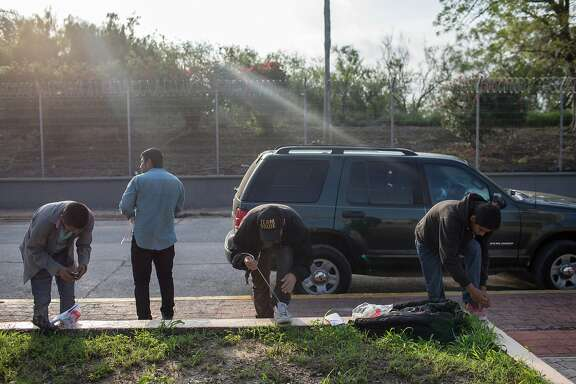 A group of men gather their belongings and lace up their shoes in Matamoros, Mexico after being deported from Brownsville, Texas, June 23, 2018. The president�s repeated descriptions of a chaotic, crime-ridden border have frustrated millions of Americans who live and work on the Southwest frontier; in Brownsville, many say that the illegal immigration �crisis� is largely a fiction. (Tamir Kalifa/The New York Times)