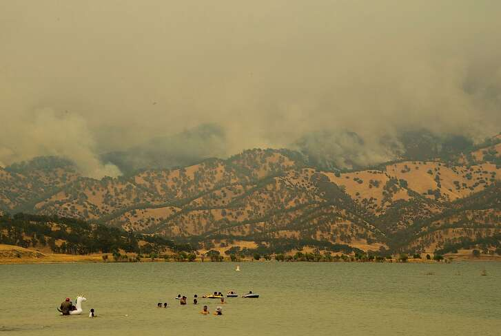A wildfire burns near Lake Berryessa in Napa, Calif., Sunday, July 1, 2018. Smoke from the Yolo County fire was contributing to poor air quality in Napa, Sonoma, San Mateo and San Francisco counties, according to the National Weather Service. (Paul Kitagaki Jr./The Sacramento Bee via AP)