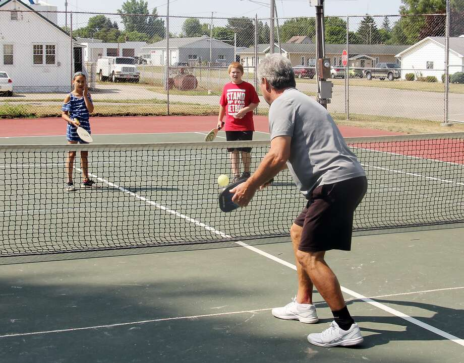 Pickleball pro, Jon Chamberlain of Port Austin, returns a shot as partners Zoey McCrea, 9, and Warren DeBoer, 10, both of Bad Axe, plan their next move. A handful of the Bad Axe Park and Rec kids were stopped by the tennis courts in Bad Axe on Wednesday to learn a new, popular game — pickleball. Photo: Bradley Massman/Huron Daily Tribune