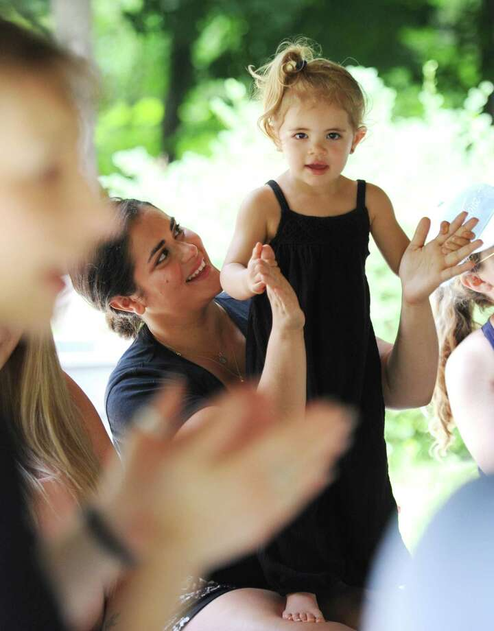 Cos Cob's Tatiana Mohrin and her daughter, Francesca, 2, dance along to a song during the Greenwich Library Stories in the Park program at the Bruce Park Playground gazebo across the street from the Bruce Museum in Greenwich, Conn. Wednesday, July 11, 2018. Dozens of children and their caretakers crowded into the gazebo for readings of children's books and interactive songs for babies, toddlers, and preschoolers. Photo: Tyler Sizemore / Hearst Connecticut Media / Greenwich Time