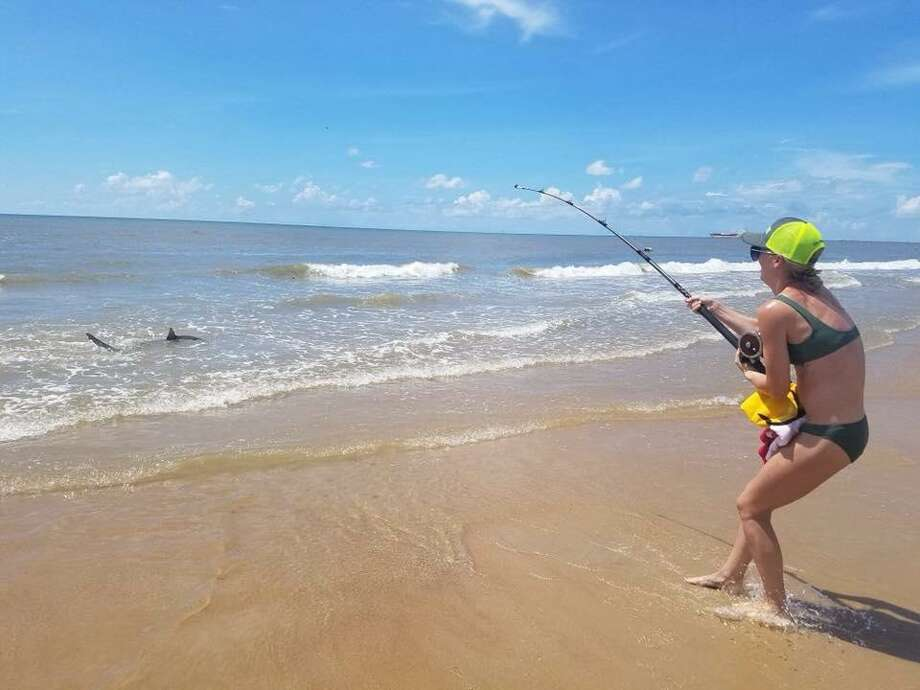 Conroe resident Lauren Biggers works to reel in a 7-foot black tip shark at Surfside Beach. Photo: Courtesy Of Lauren Biggers