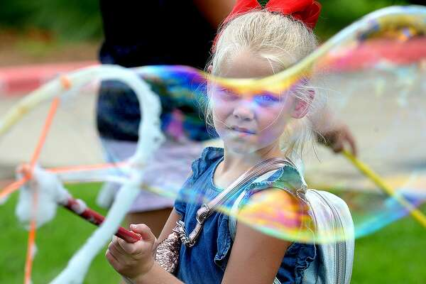 Ava Bergeron watches as her large bubble makes its way through the air during the Bubble Day event at Rogers Park. Texas Energy Museum partners with the Beaumont Public Library for the summer series, which combines the fun of bubble-making with science. Wednesday, July 11, 2018 Kim Brent/The Enterprise
