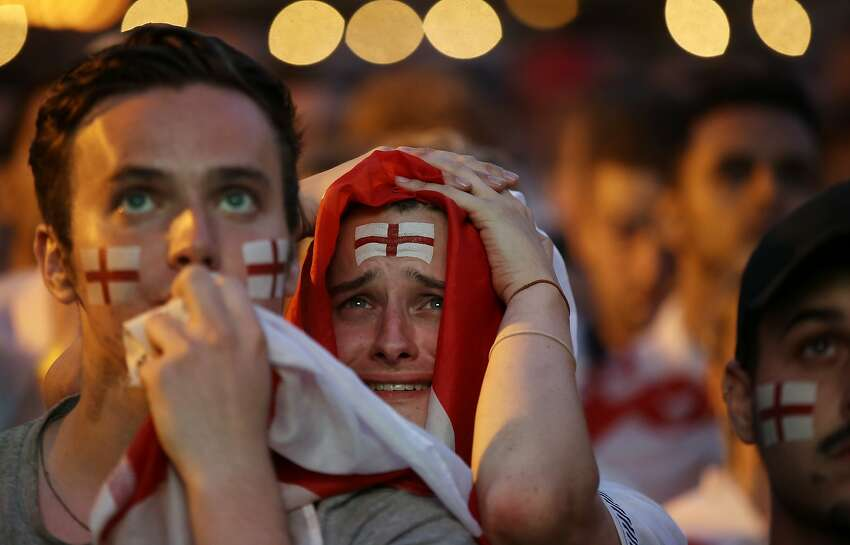 England soccer fans react after Croatia scored their side's second goal as they watch a live broadcast on a big screen of the semifinal match between Croatia and England at the 2018 soccer World Cup, in Flat Iron Square, south London, Wednesday, July 11, 2018.