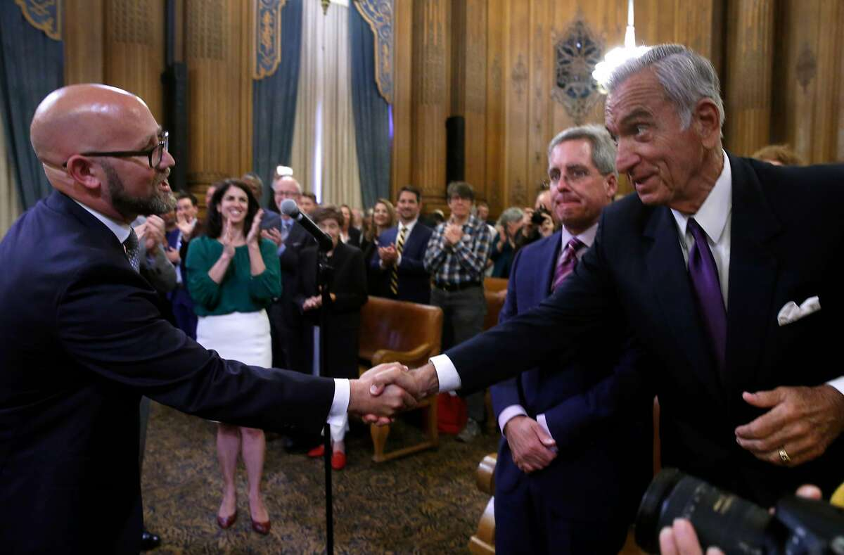 Rafael Mandelman shakes hands with former Mayor Art Agnos after Mandelman is sworn in by City Attorney Dennis Herrera as Supervisor for District 8 at City Hall in San Francisco, Calif. on Wednesday, July 11, 2018.