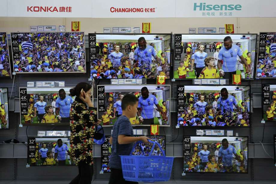 "A woman and a child pass Chinese brands of flat screen TVs on display at a hypermarket in Beijing, Wednesday, July 11, 2018. China's government has criticized the latest U.S. threat of a tariff hike as ""totally unacceptable"" and vowed to retaliate in their escalating trade war. The Commerce Ministry on Wednesday gave no details, but Beijing responded to last week's U.S. tariff hike on $34 billion of imports from China by increasing its own duties on the same amount of American goods. Photo: Andy Wong /Associated Press / Copyright 2018 The Associated Press. All rights reserved."