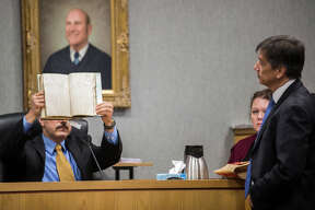 Dr. Thomas Weiser, Haruka Weiser's father, identifies a book that is in evidence under questioning from prosecutor Guillermo Gonzalez, during Meechaiel Criner's capital murder trial Wednesday, July 11, 2018 in Austin, Texas. Criner, a 17-year-old foster care runaway at the time, is accused of killing University of Texas student Haruka Weiser in April 2016. He faces a sentence of life in prison if convicted. (Ricardo Brazziell/Austin American-Statesman via AP)