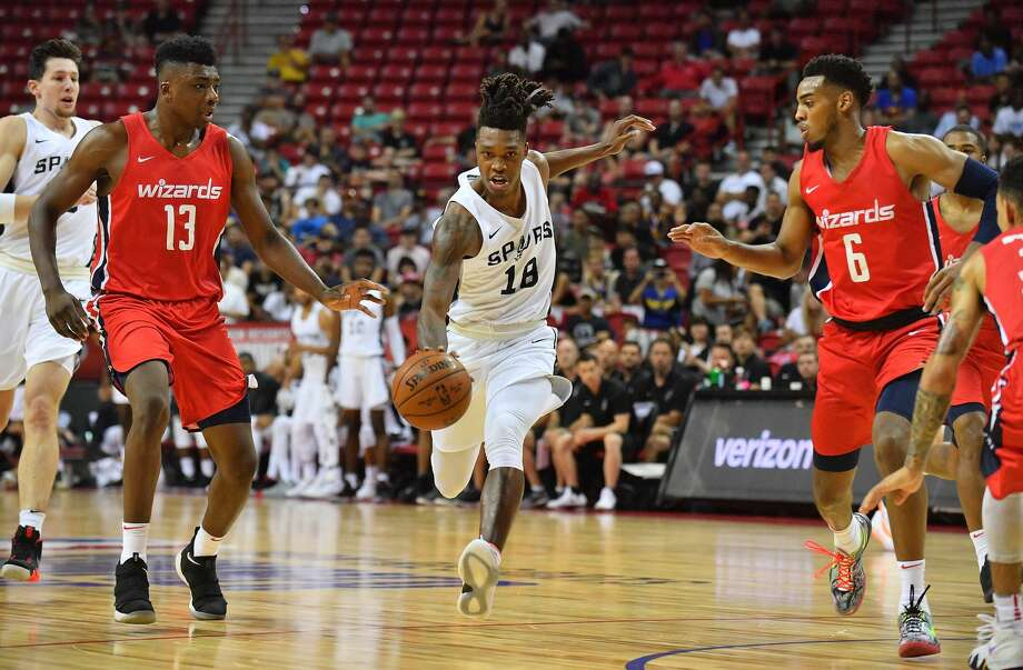 LAS VEGAS, NV - JULY 08:  Lonnie Walker IV #18 of the San Antonio Spurs dribbles against Thomas Bryant #13 and Troy Brown Jr. #6 of the Washington Wizards during the 2018 NBA Summer League at the Thomas & Mack Center on July 8, 2018 in Las Vegas, Nevada. NOTE TO USER: User expressly acknowledges and agrees that, by downloading and or using this photograph, User is consenting to the terms and conditions of the Getty Images License Agreement.  (Photo by Sam Wasson/Getty Images) Photo: Sam Wasson/Getty Images