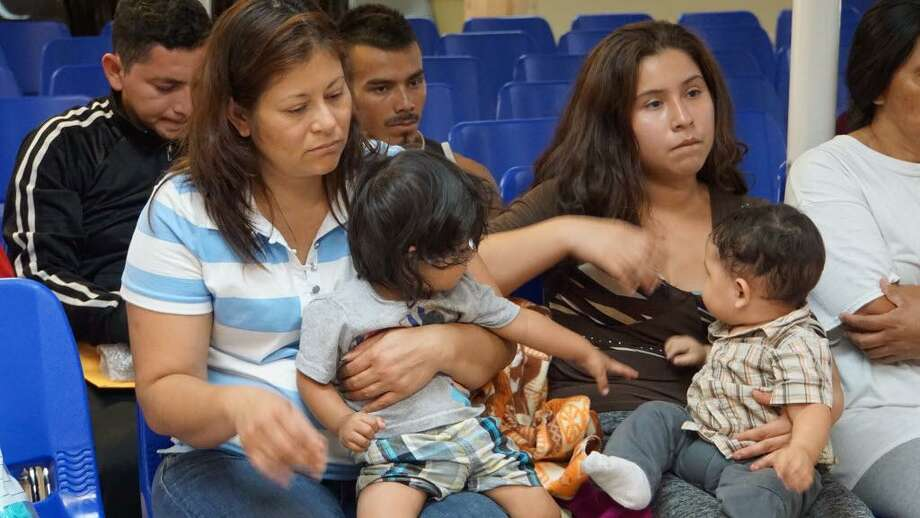 """Mothers and children wait to be assisted by volunteers in a humanitarian center in the border town of McAllen on June 15. Officials have ordered DNA tests on """"under 3,000"""" detained children who remain separated from their migrant parents, in an effort to reunite families, a top official said on July 5. Photo: /"""