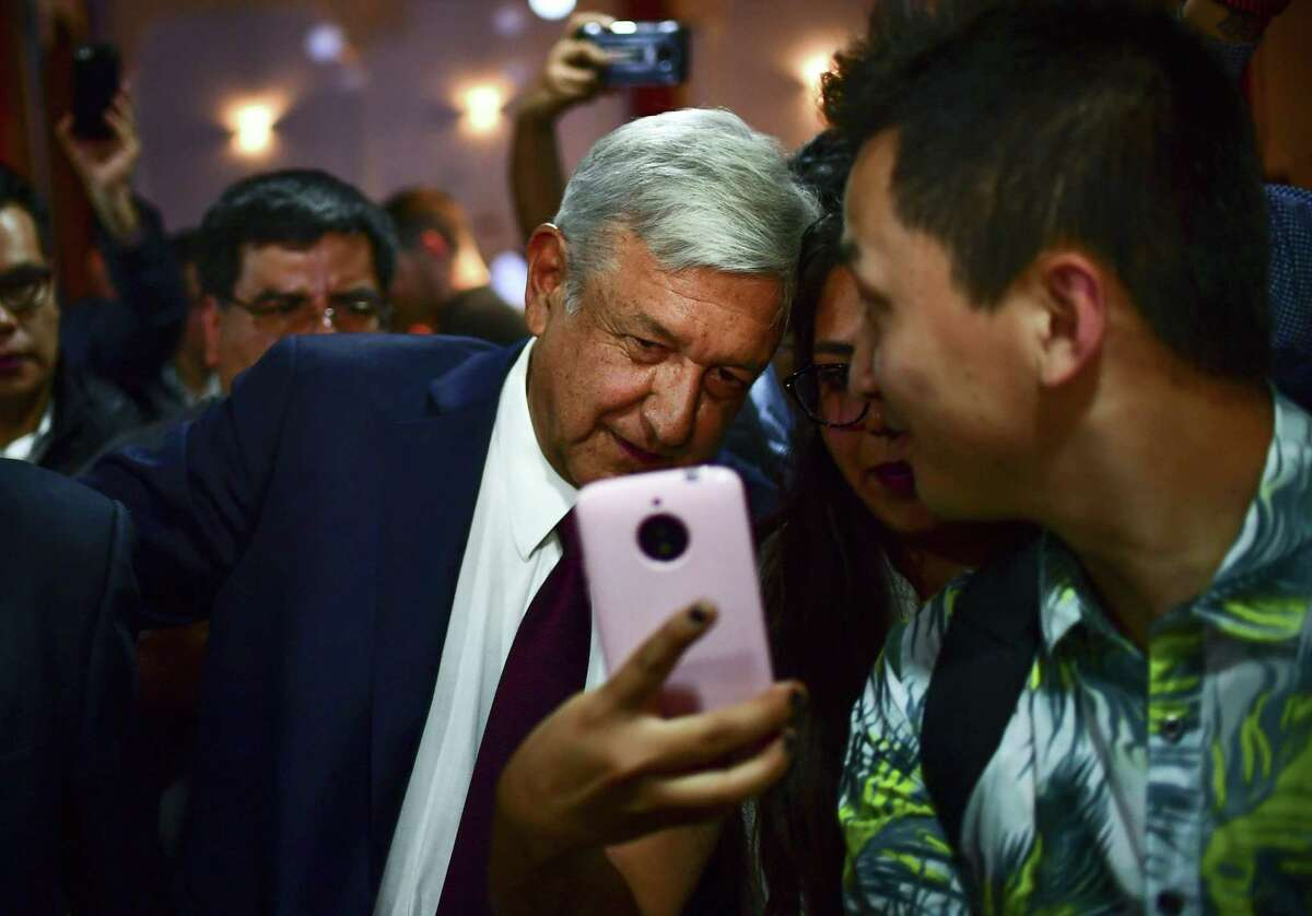 Mexico's President-elect Andres Manuel Lopez Obrador (AMLO) poses for a selfie with a supporter after a press conference in Mexico City, on July 5, 2018. The promise of Mexico's President-elect of governing
