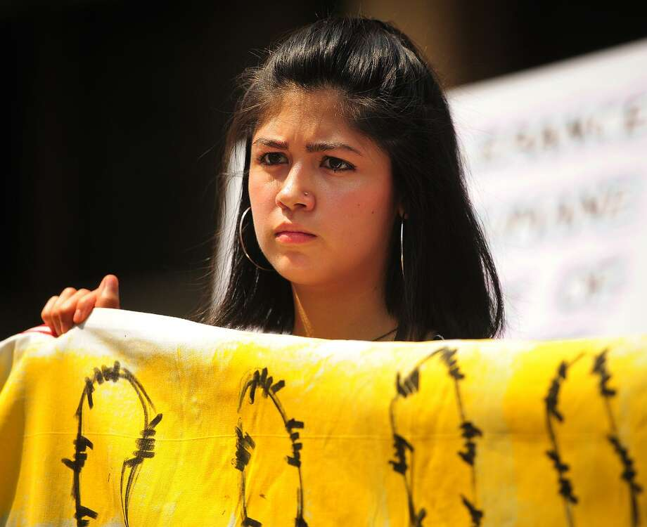 Yale student Larissa Martinez, 21, an undocumented immigrant from Mexico, holds a banner at an immigration rally outside the Federal Courthouse in Bridgeport, Conn. on Wednesday, July 11, 2018. Two asylum seeking children separated from their parents in Texas attended an emergency hearing at the courthouse on Wednesday. Photo: Brian A. Pounds / Hearst Connecticut Media / Connecticut Post