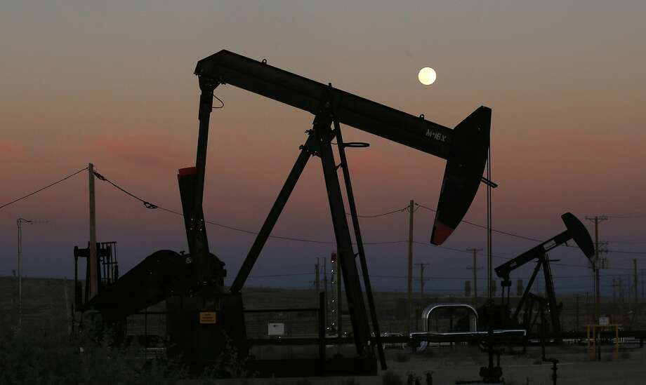 FILE - In this June 8, 2017, file photo, oil derricks are busy pumping as the moon rises near the La Paloma Generating Station in McKittrick, Calif.  Photo: Gary Kazanjian, Associated Press