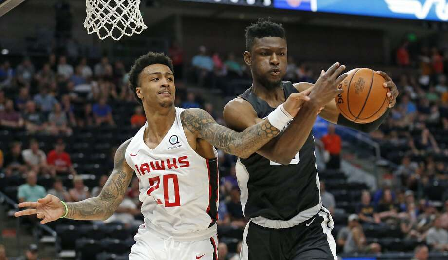 San Antonio Spurs forward Chimezie Metu, right, pulls down a rebound as Atlanta Hawks forward John Collins (20) defends during the first half of an NBA summer league basketball game Tuesday, July 3, 2018, in Salt Lake City. (AP Photo/Rick Bowmer) Photo: Rick Bowmer, Associated Press