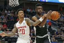 San Antonio Spurs forward Chimezie Metu, right, pulls down a rebound as Atlanta Hawks forward John Collins (20) defends during the first half of an NBA summer league basketball game Tuesday, July 3, 2018, in Salt Lake City. (AP Photo/Rick Bowmer)