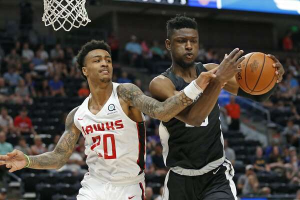 San Antonio Spurs forward Chimezie Metu, right, pulls down a rebound as Atlanta Hawks forward John Collins (20) defends during the first half of an NBA summer league basketball game Tuesday, July 3, 2018, in Salt Lake City. (AP Photo/Rick Bowmer)