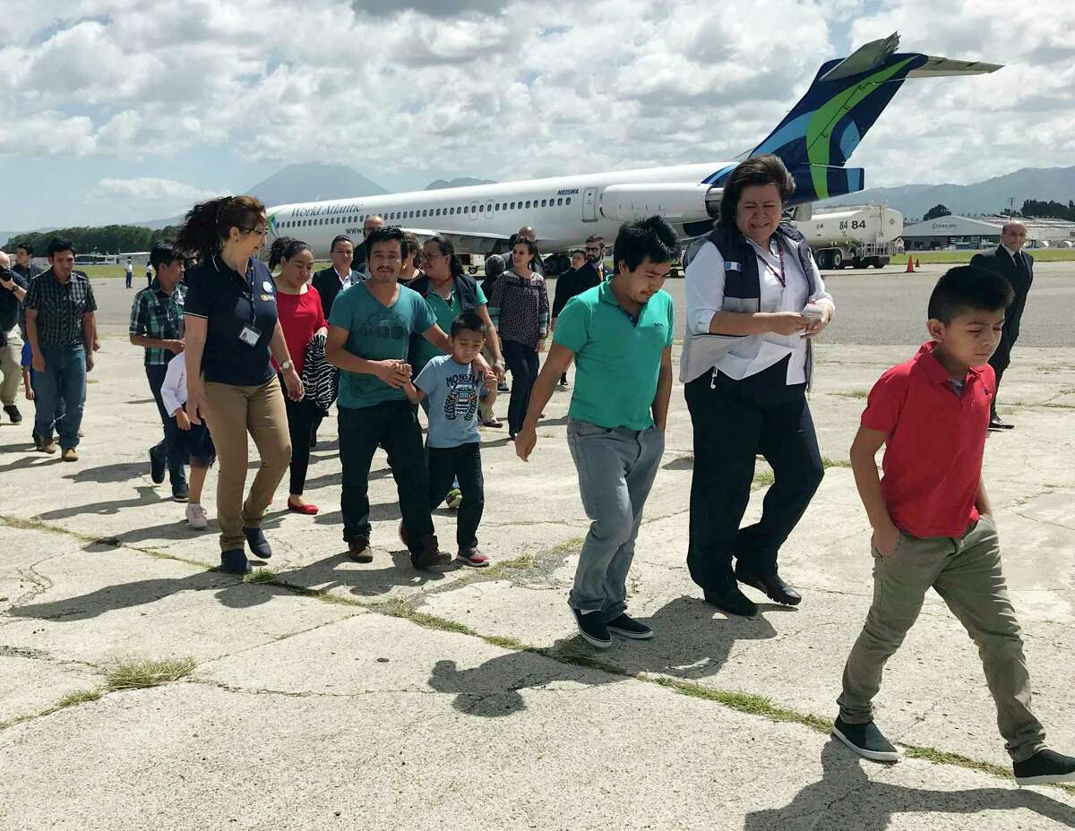 Families separated under President Donald Trump administration?'s zero tolerance policy return home to Guatemala City, Guatemala, Tuesday, July 10, 2018, after being deported from the United States. After lining up on the tarmac, they headed to a processing center where they were screened and given identification before being released back into the country. (AP Photo/Colleen Long)