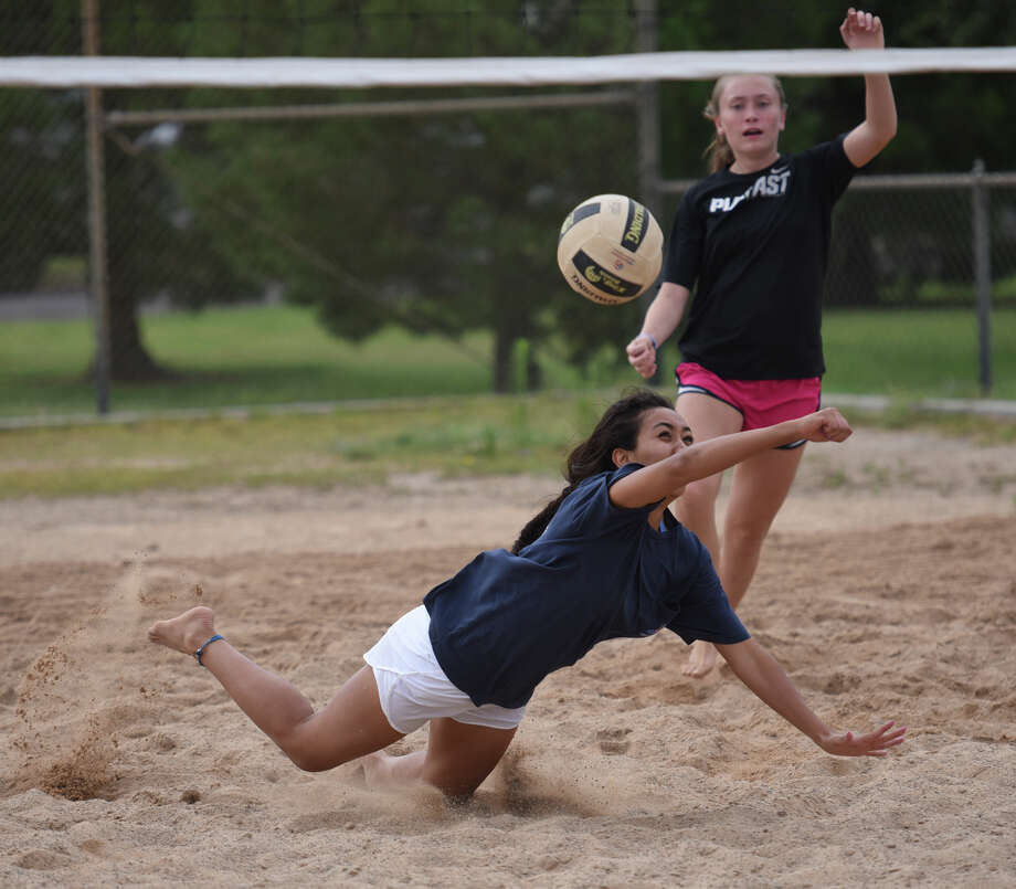 Alyssa Sotelo dives for the ball in front of teammate Brylee Awbrey during beach volleyball team practice July 9, 2018, at Ulmer Park. James Durbin/Reporter-Telegram Photo: James Durbin / ? 2018 Midland Reporter-Telegram. All Rights Reserved.