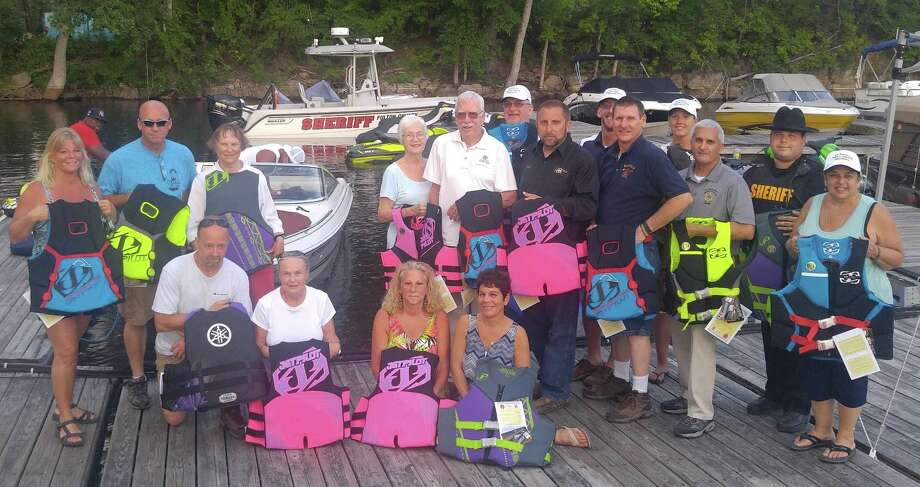 Sacandaga Safe Lake Initiative members and others display life vests donated this summer by the Yamaha Motor Corp. at the Grandview Marina in Mayfield, Fulton County. The jackets will be used by law enforcement personnel. Officers patrolling the Great Sacandaga Lake can provide recreation users with the life vests rather that fines. (Fulton County Sheriff's Department)