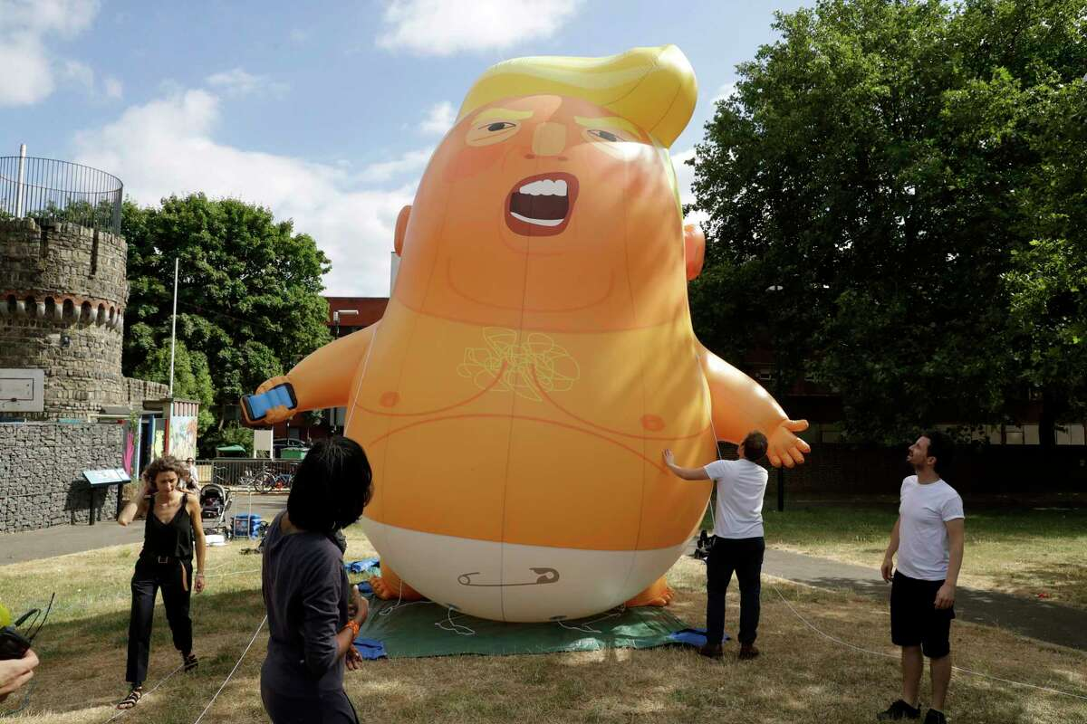 In this photo taken on Tuesday, July 10, 2018, a six-meter high cartoon baby blimp of U.S. President Donald Trump stands inflated during a practice session in Bingfield Park, north London. Trump will get the red carpet treatment on his brief visit to England that begins Thursday: Military bands at a gala dinner, lunch with the prime minister at her country place, then tea with the queen at Windsor Castle before flying off to one of his golf clubs in Scotland. But trip planners may go out of their way to shield Trump from viewing another aspect of the greeting: an oversize balloon depicting the president as an angry baby in a diaper that will be flown from Parliament Square during what are expected to be massive gatherings of protesters opposed to Trump?'s presence. (AP Photo/Matt Dunham)
