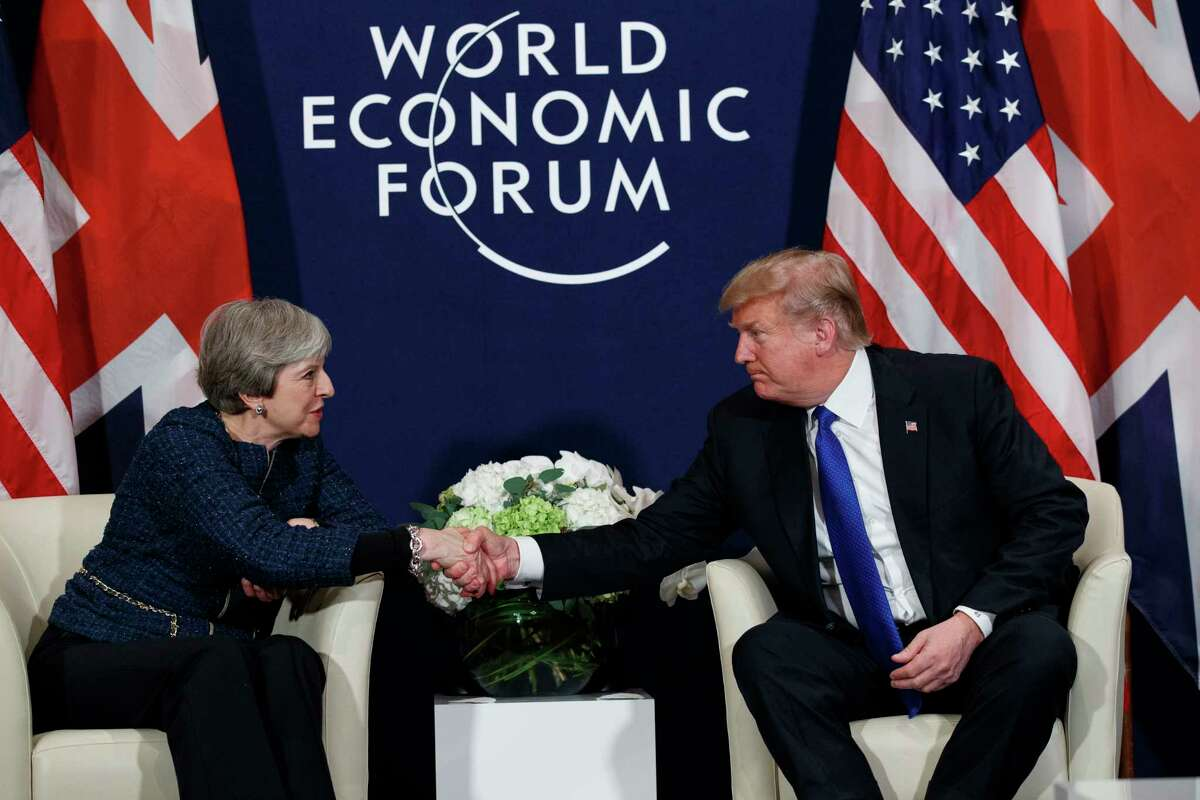 FILE - In this file photo from Jan. 25, 2018, President Donald Trump meets with British Prime Minister Theresa May at the World Economic Forum in Davos, Switzerland. Trump will get the red carpet treatment on his brief visit to the U.K. beginning Thursday, July 12, 2018. Military bands at a gala dinner, lunch with the prime minister at her country residence, then tea with the queen at Windsor Castle before flying off to one of his golf clubs in Scotland. (AP Photo/Evan Vucci, File)