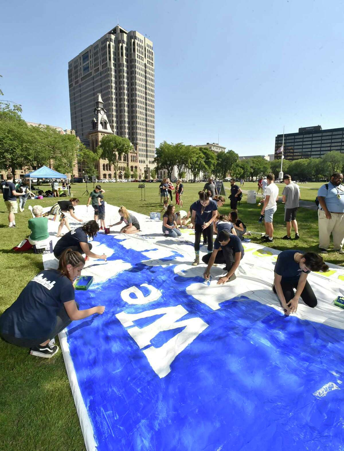 Jewish, Muslim and Christian teenagers from Israel and Palestine paint a 48-foot sign on the New Haven Green.