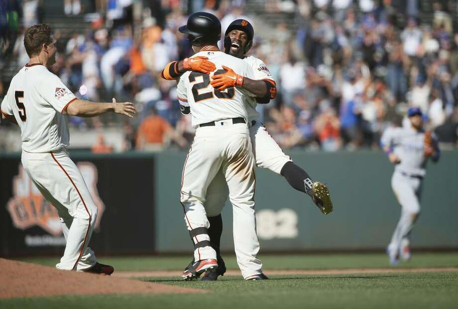 San Francisco Giants catcher Buster Posey (28) and Giants center fielder Andrew McCutchen (22) hug after Posey scored the game winning hit, ending MLB game between the Giants and Chicago Cubs in the bottom of the 13th inning at AT&T Park, Wednesday, July 11, 2018, in San Francisco, Calif. Photo: Santiago Mejia / The Chronicle / ONLINE_YES