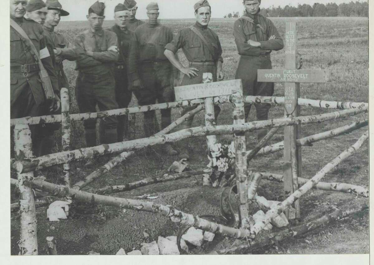 American soldiers stand at the grave of Lt. Quentin Roosevelt in 1918. The cross was put in place by Chaplain Francis P. Duffy of the New York National Guard's 69th Infantry. The rustic railing around the grave was erected by soldiers of the U.S. 32nd Divison. (U.S. Army Signal Corps)
