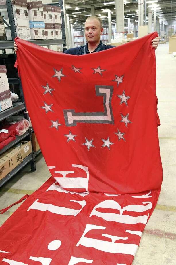 Scott Chidgey unfurls a banner as North East ISD employees sort through Lee-branded items from Robert E. Lee High School on July 11, 2018. Photo: Tom Reel, Staff / San Antonio Express-News / 2017 SAN ANTONIO EXPRESS-NEWS