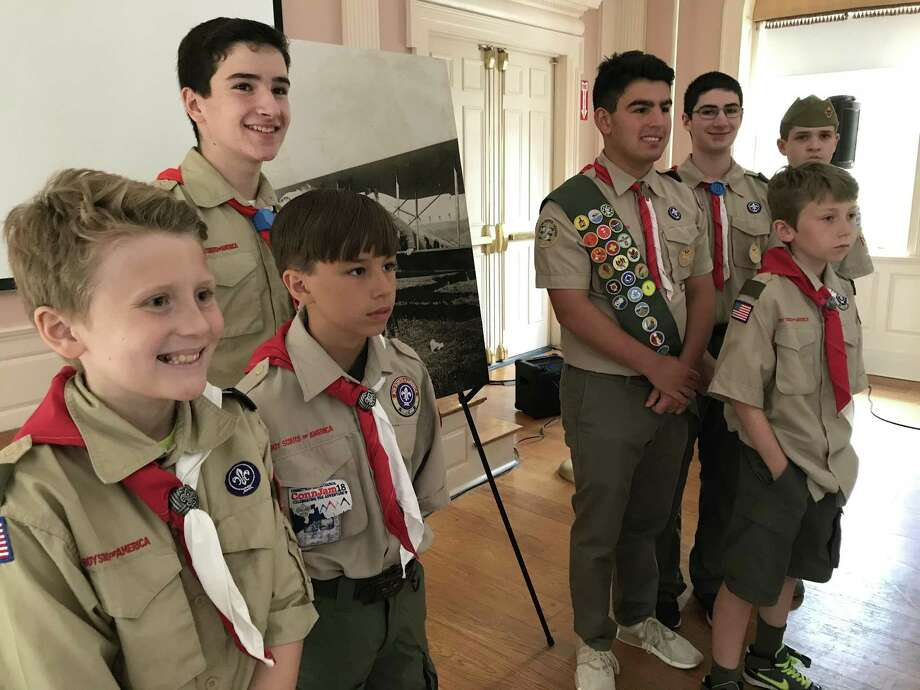 Boy Scout Troop 41 of Woodbridge stands in front of a portrait of Lt. Gilbert Jerome, a fighter pilot in World War I and a pivotal figure in local scouting. Photo: Brian Zahn / Hearst Connecticut Media