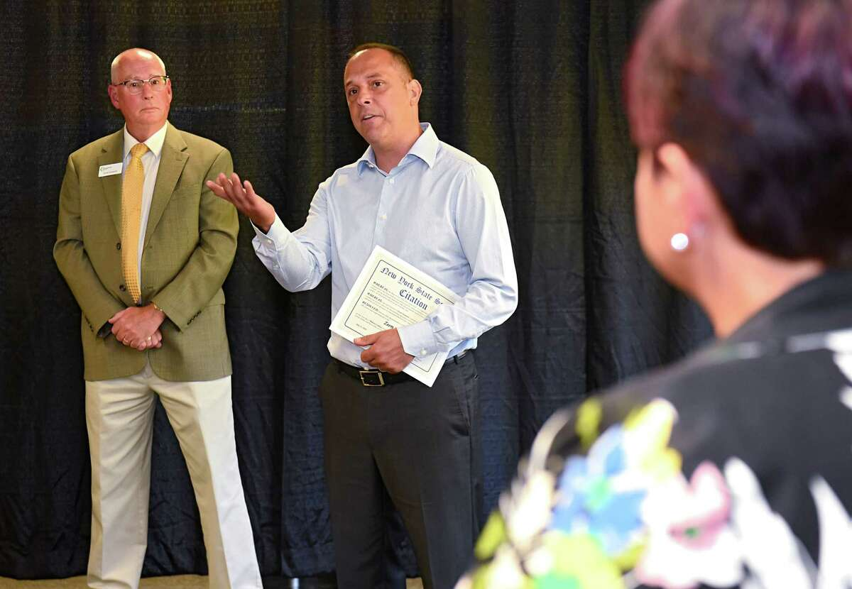 Zeem Solutions CEO Paul Gioupis, center, speaks during a ribbon cutting celebration at Zeem Solutions on Wednesday, July 11, 2018 in Schenectady, N.Y. Scott Osswald of Capital Region Chamber listens at left. Councilwoman Leesa Perazzo listens at right. Zeem is a service provider that offers validated Commercial Electric VehicleOs for fleet operators in the USA. (Lori Van Buren/Times Union)