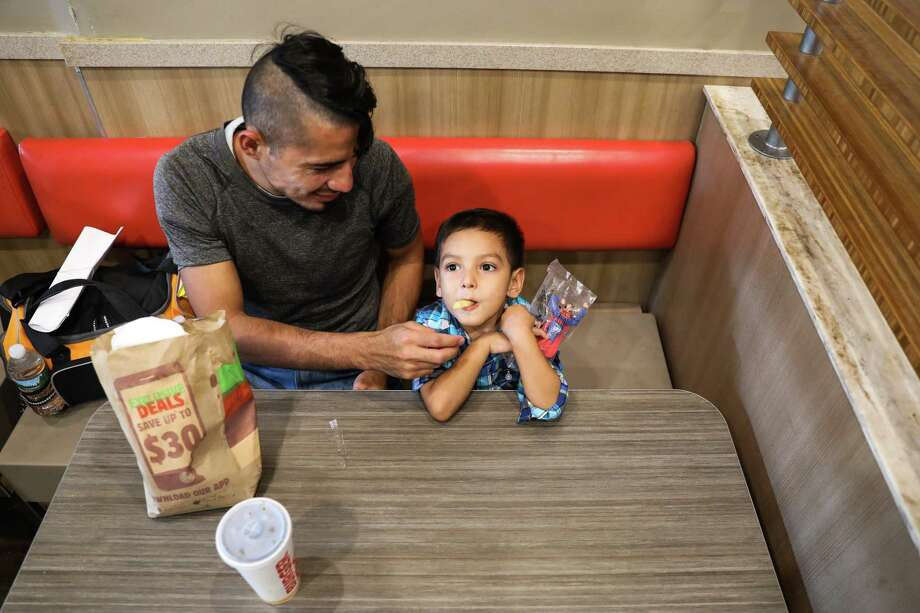 Denis Rivas, left, an immigrant who was reunited earlier in the day with his son, Joshua, 4, right, grabs a meal for them both in New York, July 11, 2018. Denis Rivas, who had last seen his son just over a month ago — said they were separated the day after they crossed a bridge at the border and turned themselves over to the authorities. A trickle of families separated at the border were reunited Wednesday in New York, a day after a court deadline, while thousands remained apart. (Marian Carrasquero/The New York Times) Photo: MARIAN CARRASQUERO / NYTNS