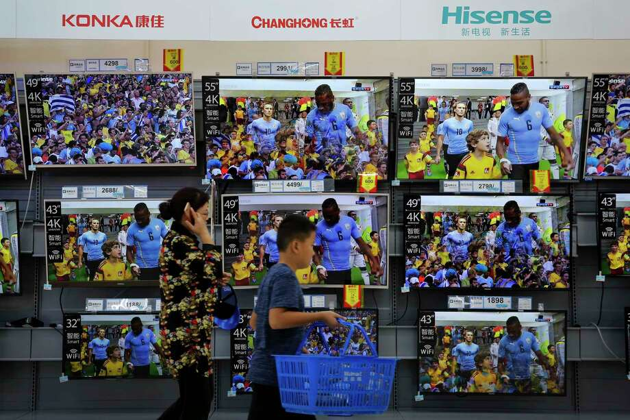 "A woman and a child pass Chinese brands of flat screen TVs on display at a hypermarket in Beijing, Wednesday, July 11, 2018. China's government has criticized the latest U.S. threat of a tariff hike as ""totally unacceptable"" and vowed to retaliate in their escalating trade war. The Commerce Ministry on Wednesday gave no details, but Beijing responded to last week's U.S. tariff hike on $34 billion of imports from China by increasing its own duties on the same amount of American goods. (AP Photo/Andy Wong) Photo: Andy Wong / Copyright 2018 The Associated Press. All rights reserved."