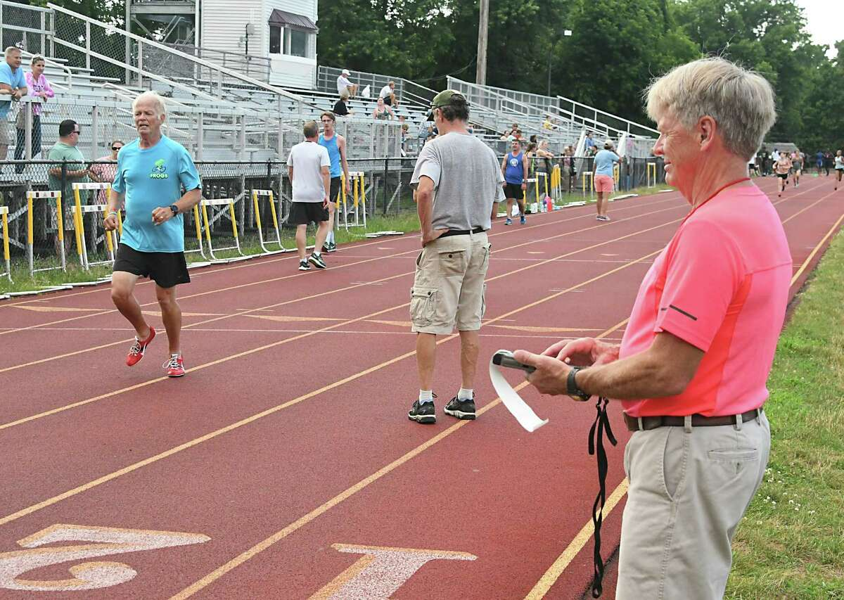 Founder Frank Myers, left, finishes a mile run as his brother and founder Donnie Myers, right, records his time during the weekly summer track meet at Colonie High School on Tuesday, July 10, 2018 in Colonie, N.Y. (Lori Van Buren/Times Union)