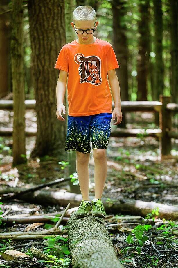 Aaron Grasman of Midland, 10, walks on a log Wednesday afternoon inside the new outdoor play area at the Chippewa Nature Center in Midland. (Katy Kildee/kkildee@mdn.net)