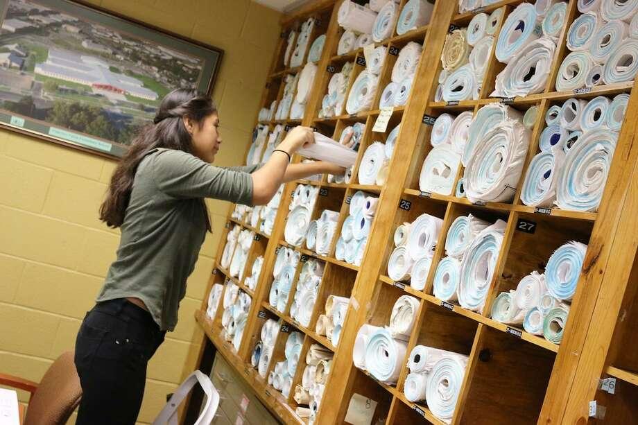 Una estudiante del programa de pasantías estudiantiles de verano del distrito escolar LISD trabaja acomodando material en un estante como parte de sus labores Photo: Foto De Cortesía /LISD