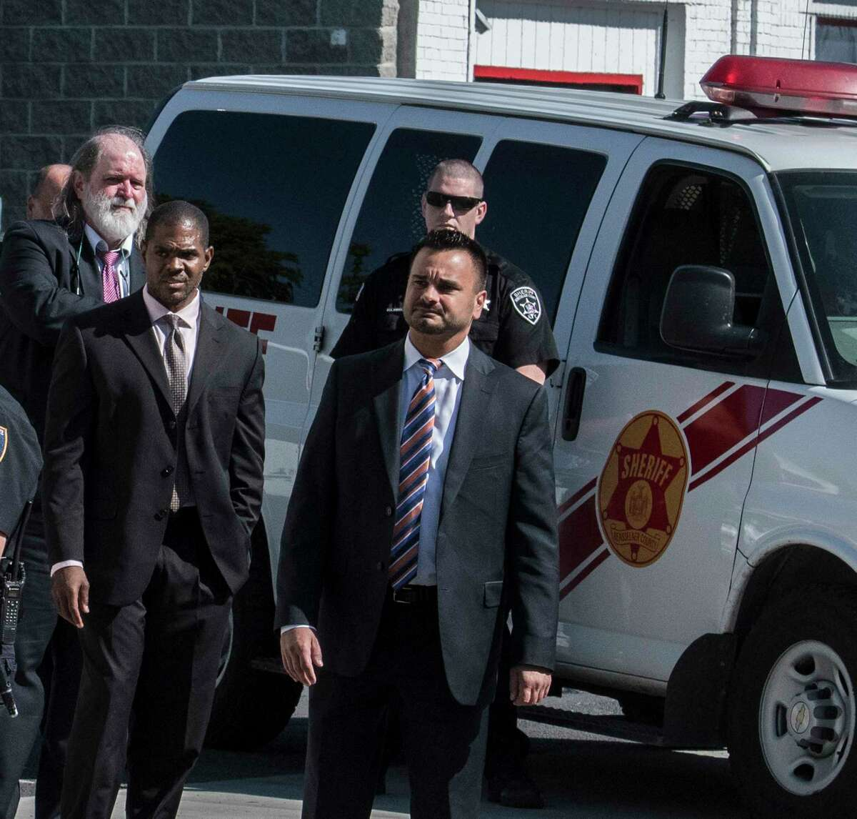 With a significant security detail New York State Supreme Court Judge Andrew Ceresia, center, looks south on 5th Avenue as a prisoner van containing Richard Wright, background, sits in sight of the entourage during a tour of the structures that were involved with the murder and arson case of Richard Wright Thursday July 12, 2018 in Troy, N.Y. (Skip Dickstein/Times Union)