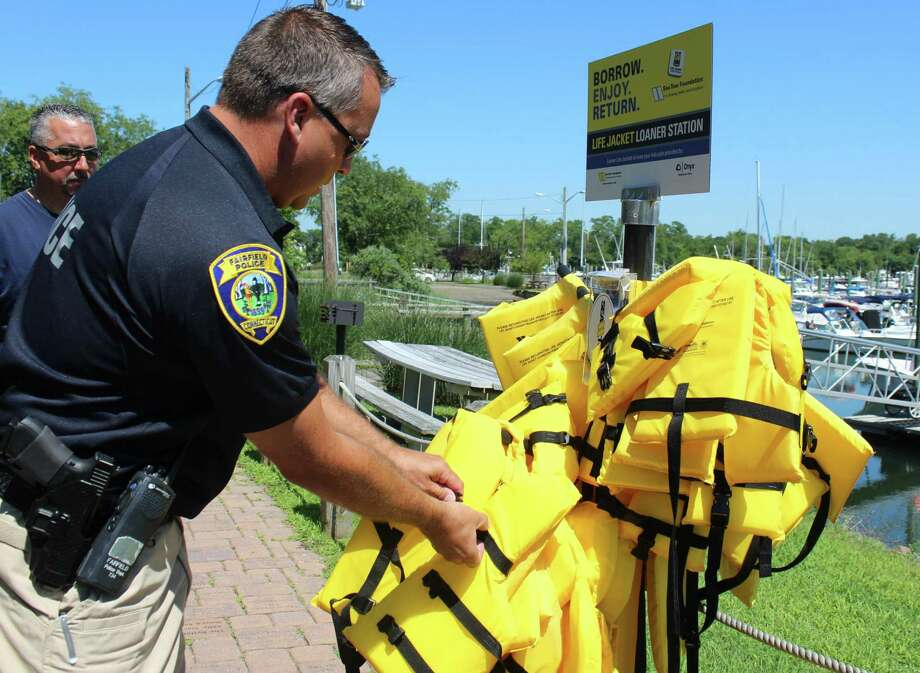 Offier James Wiltsie checks on life jackets that are available on loan to boaters, before he and Officer Keith Perham head out on the water. Fairfield,CT. 7/11/18 Photo: Genevieve Reilly / Hearst Connecticut Media / Fairfield Citizen