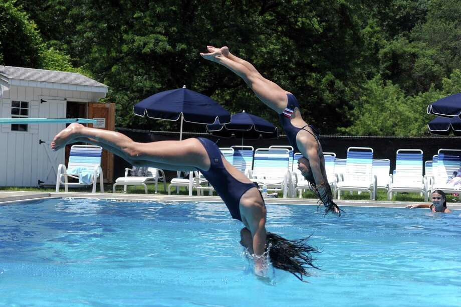 Fiona Garfield, 11, left, and Maggie Sedlack, 13, both of Darien, attempt a synchronized dive at the Newfield Swim and Tennis Club in Stamfor on July 2. Photo: Michael Cummo / Hearst Connecticut Media / Stamford Advocate