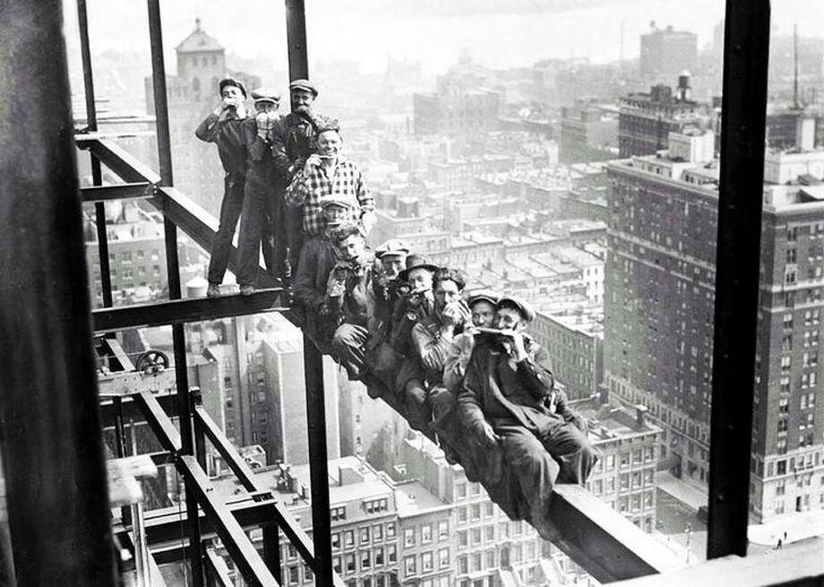 A photograph from the early part of the century shows construction workers without hard hats, despite being high above a city in clearly dangerous working conditions. Hard hats were seen as unmanly and portrayed workers as afraid. Photo: For The Intelligencer