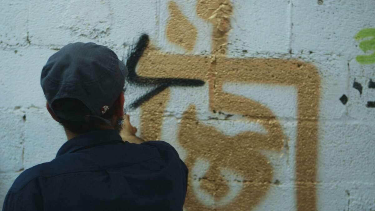 """An artist paints graffiti on a Jerusalem wall in """"Jerusalem If Forget You,"""" screening at the July 19-Aug. 5 S.F. Jewish Film Festival."""