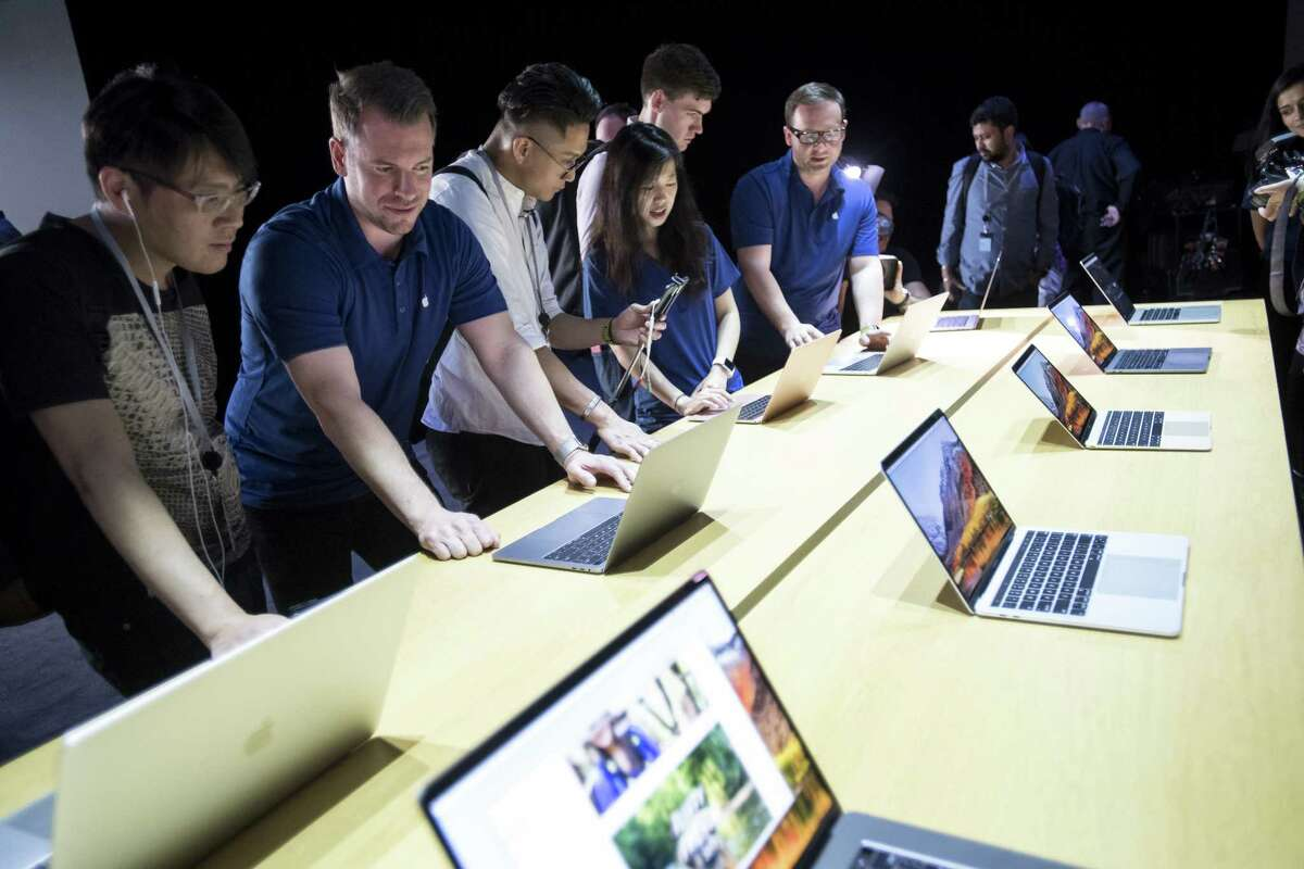 Attendees of the Apple Worldwide Developers Conference in San Jose, Calif., look at new MacBook Pro laptops in June 2017.