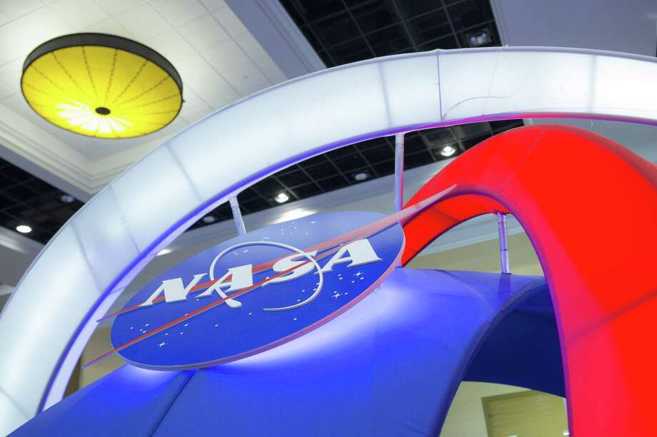 Signage is displayed at the National Aeronautics and Space Administration (NASA) booth during the 32nd Space Symposium in Colorado Springs, Colorado, U.S., on Tuesday, April 12, 2016. Photo: Bloomberg Photo By Matthew Staver. / Bloomberg