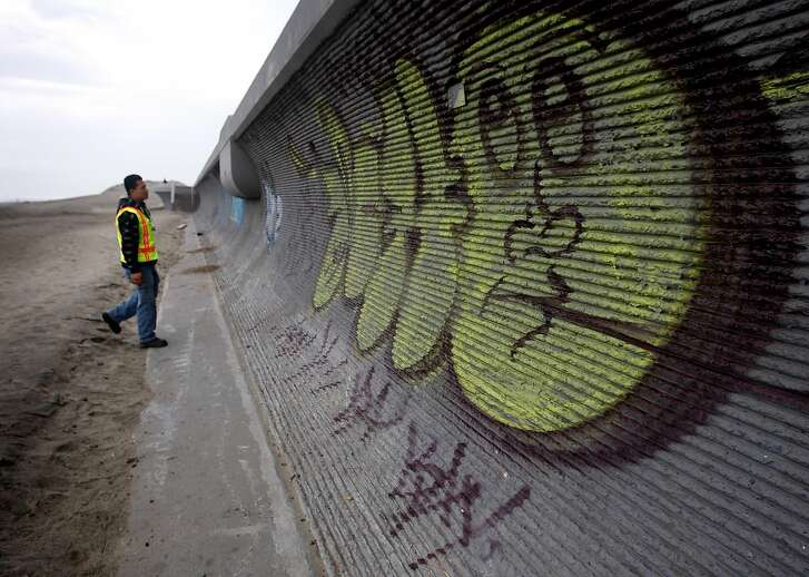 Jonathan Vaing, with the DPW's grafitti abatement unit, views the work of taggers on a seawall at Ocean Beach in San Francisco, Calif., on Friday, Jan. 8, 2010. A group of juvenile offenders, under the supervision of police officers, will paint over the grafitti on Sunday.