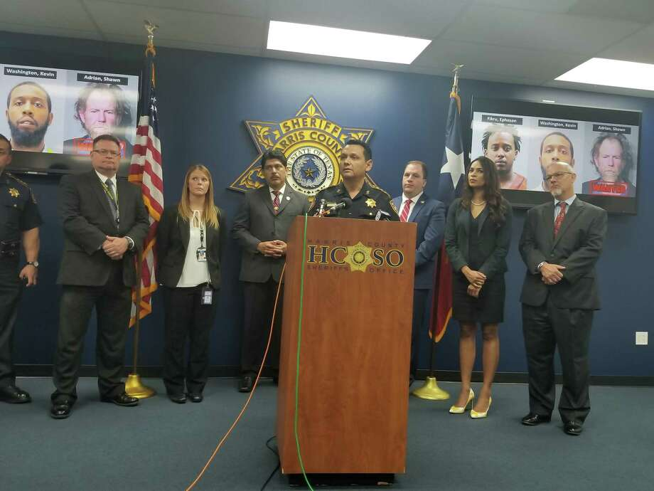 Harris County Sheriff Ed Gonzalez, center, and Sgt. Joshua Nowitz with the Sheriff's Office Financial Crimes Unit, next to the Texas flag, help provide details of a fraud case that involved the use of a fake Florida license. Photo: Elizabeth Myong