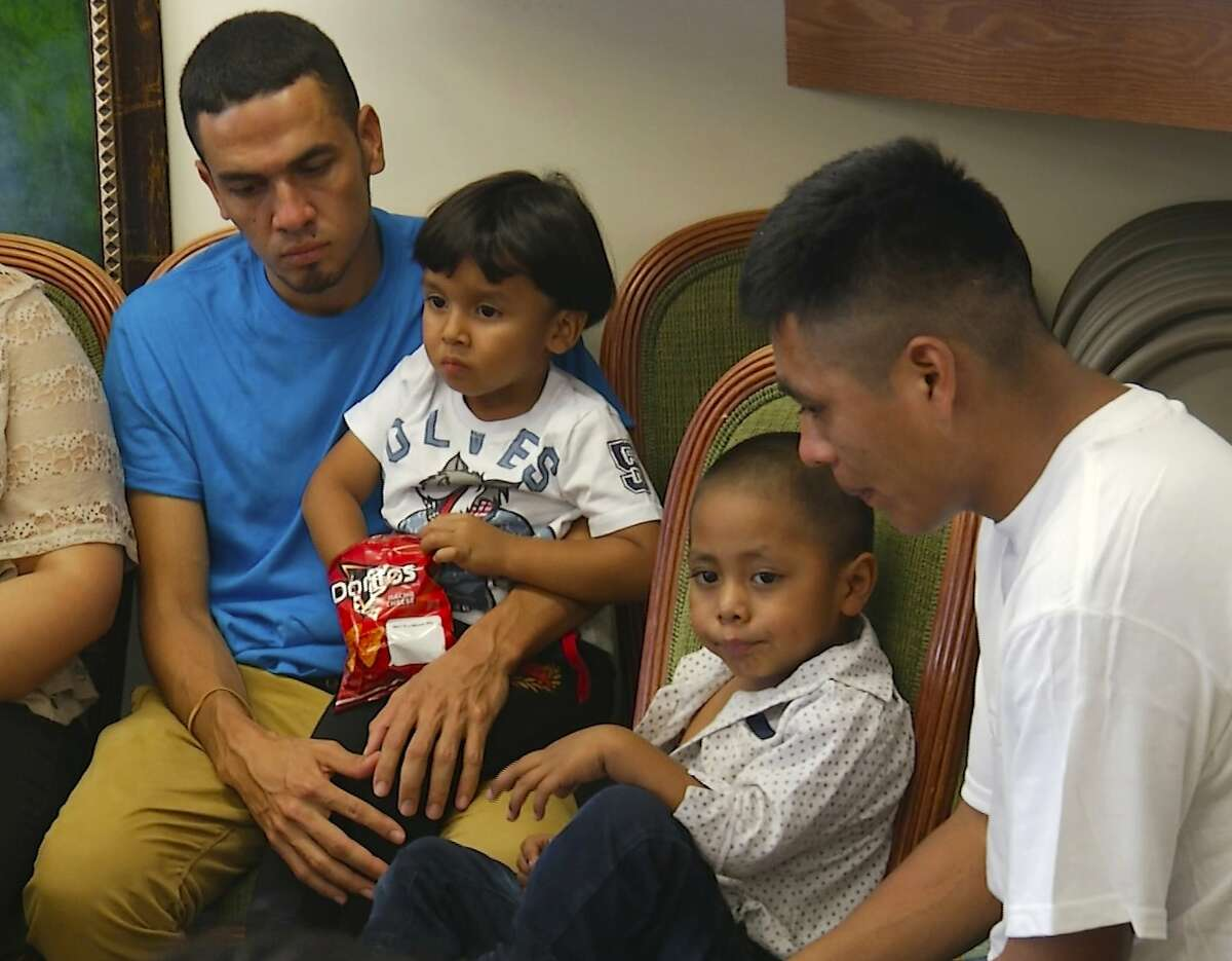 In this image taken from video, Javier Garrido Martinez, left and Alan Garcia, right, sit with their 4-year-sons at a news conference in New York, Wednesday, July 11, 2018. They men were reunited with their children after almost two months of separation, Authorities took their boys them when they stopped at the U.S. southern border.