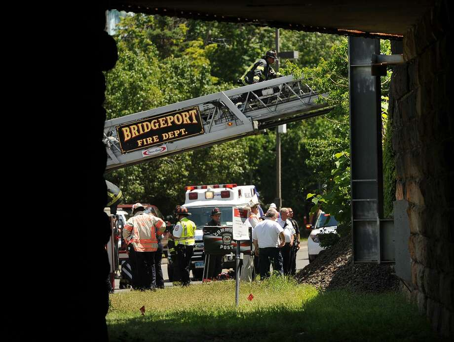 A Fairfield firefighter climbs a truck ladder to the elevated railway at the scene of a train collision on the Metro-North line behind Harbor Yard Ballpark in Bridgeport, Conn. on Thursday, July 12, 2018. Photo: Brian A. Pounds / Hearst Connecticut Media / Connecticut Post