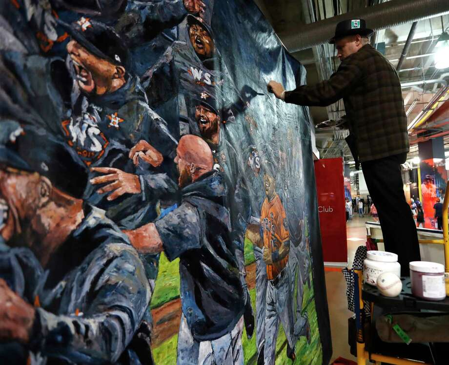 Opie Otterstad works on his giant painting of the 2017 World Series championship celebration as Astros fans walk by before the start of Tuesday's game at Minute Maid Park. Photo: Karen Warren, Houston Chronicle / © 2018 Houston Chronicle
